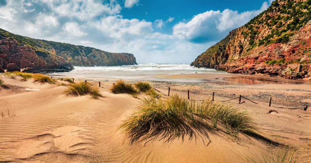 Colorful morning view of Cala Domestica beach. Sunny summer scene of Sardinia, Italy, Europe. Fantastic landscape of Canyon di Cala Domestica. Beauty of nature concept background.