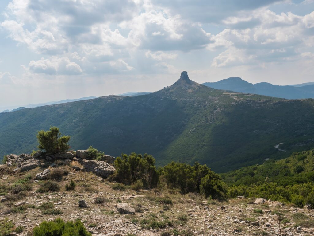 Overview of the National Park of Barbagia with limestone tower of Perda Liana, impressive rock formation on green forest hill, sardinian table mountain. Centeral Sardinia, Italy, summer day.