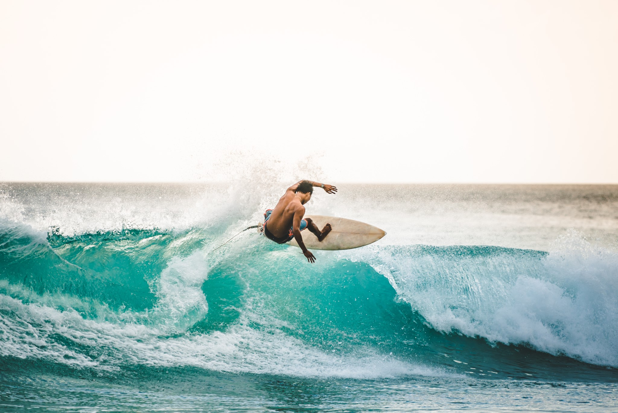 professional surfer riding waves in Bali, Indonesia. men catching waves in ocean, isolated. Surfing action water board sport. people water sport lessons and beach swimming activity on summer vacation
