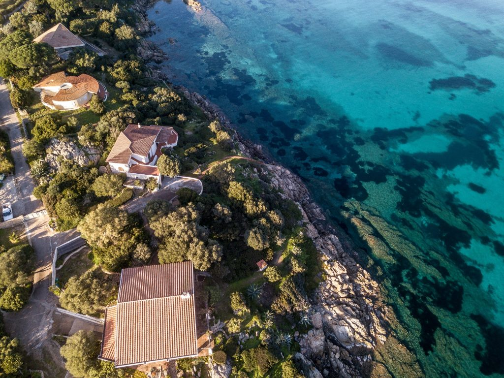 Aerial view of Cala Sassari, the small and the big coves, blue water and amazing granite rocks