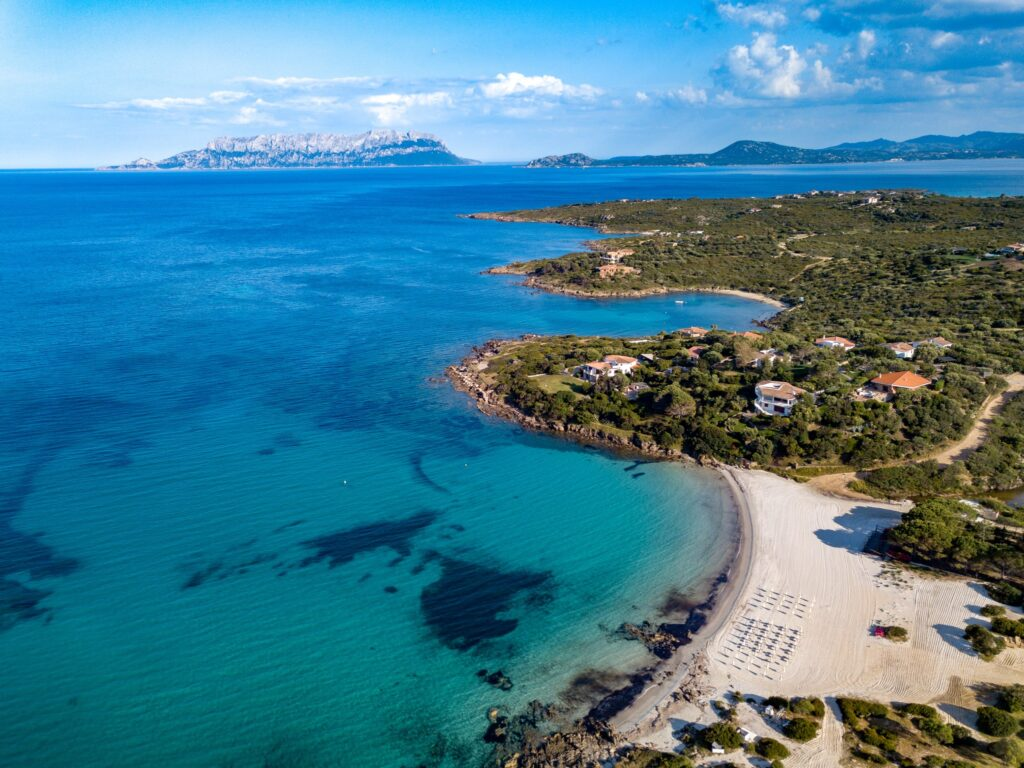 Aerial view of Sos Aranzos Beach, Golfo Aranci, nice sandy beach surrounded by granite rocks and touched by crystal clear water, North Sardinia