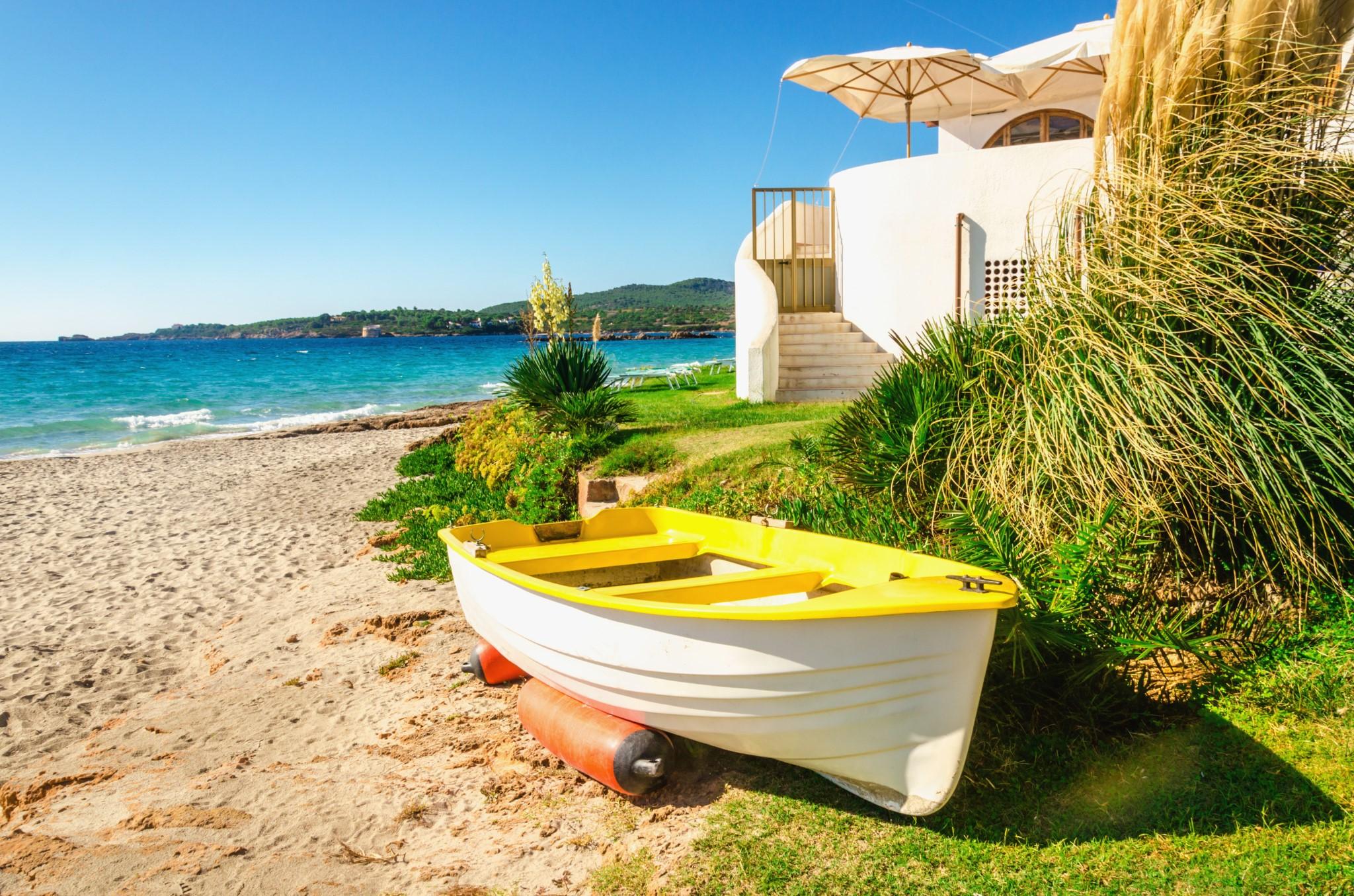Yellow boat on beautiful Bombarde beach, Alghero bay, Sardinia, Italy