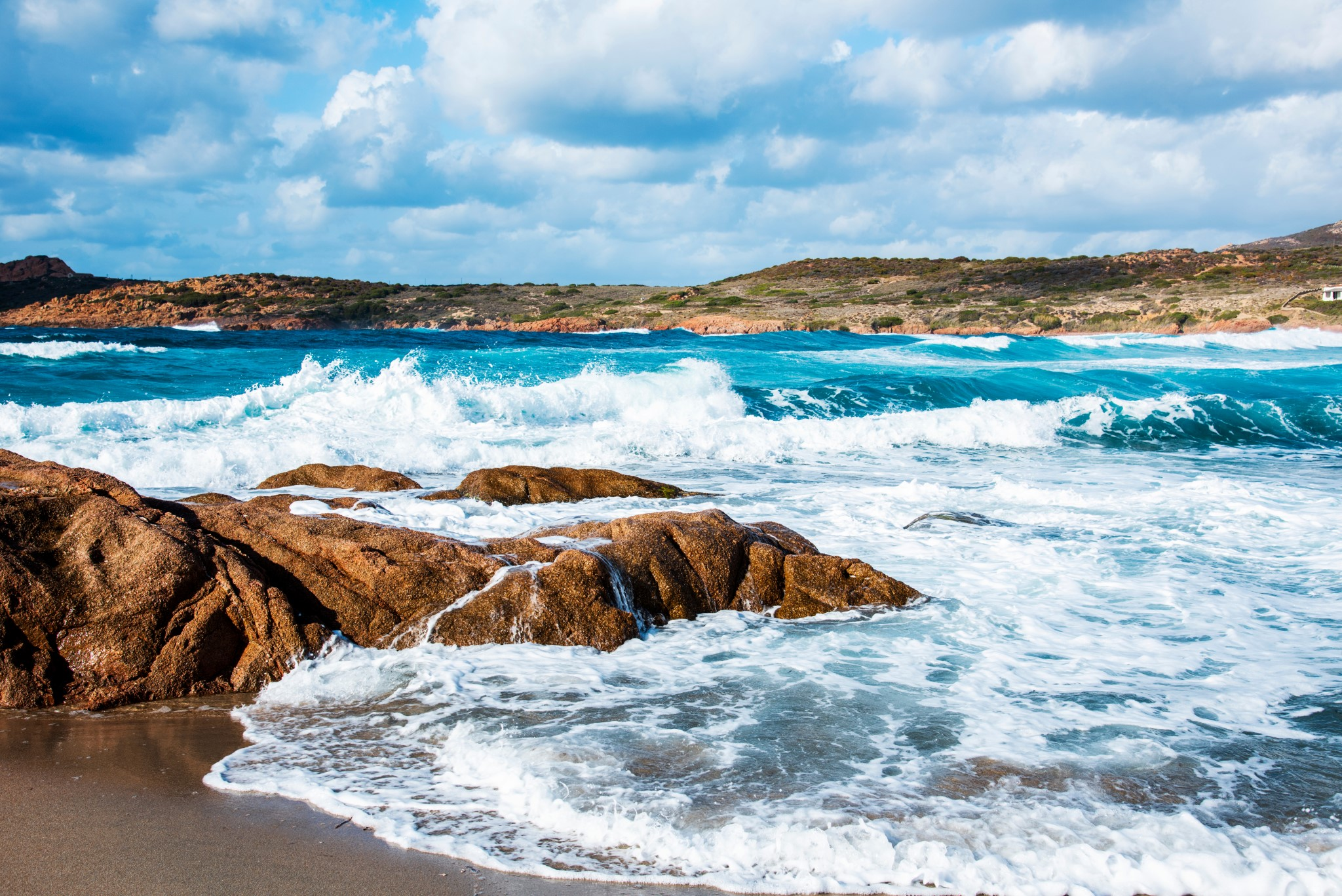 a view of the rock formations and the Mediterranean sea, with a strong swell, in La Marinedda beach, in Isola Rossa, Sardinia, Italy
