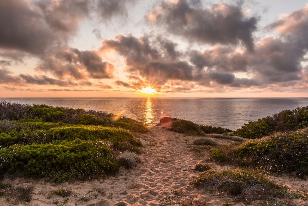 Sunset at scenic Scivu beach - Sand dunes with myrtle vegetation with the ocean in the background and sun-drenched clouds, Sardinia, Italy
