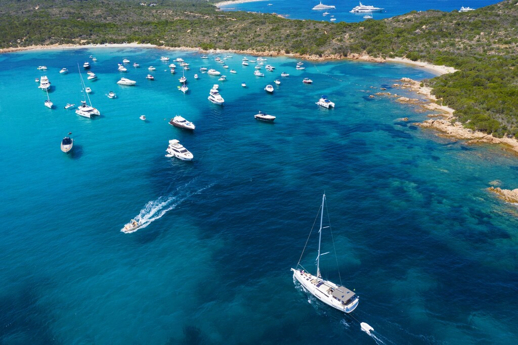 View from above, stunning aerial view of a beautiful bay full of boats and luxury yachts. A turquoise sea bathes the green and rocky coasts. Liscia Ruja, Emerald Coast (Costa Smeralda) Sardinia, Italy