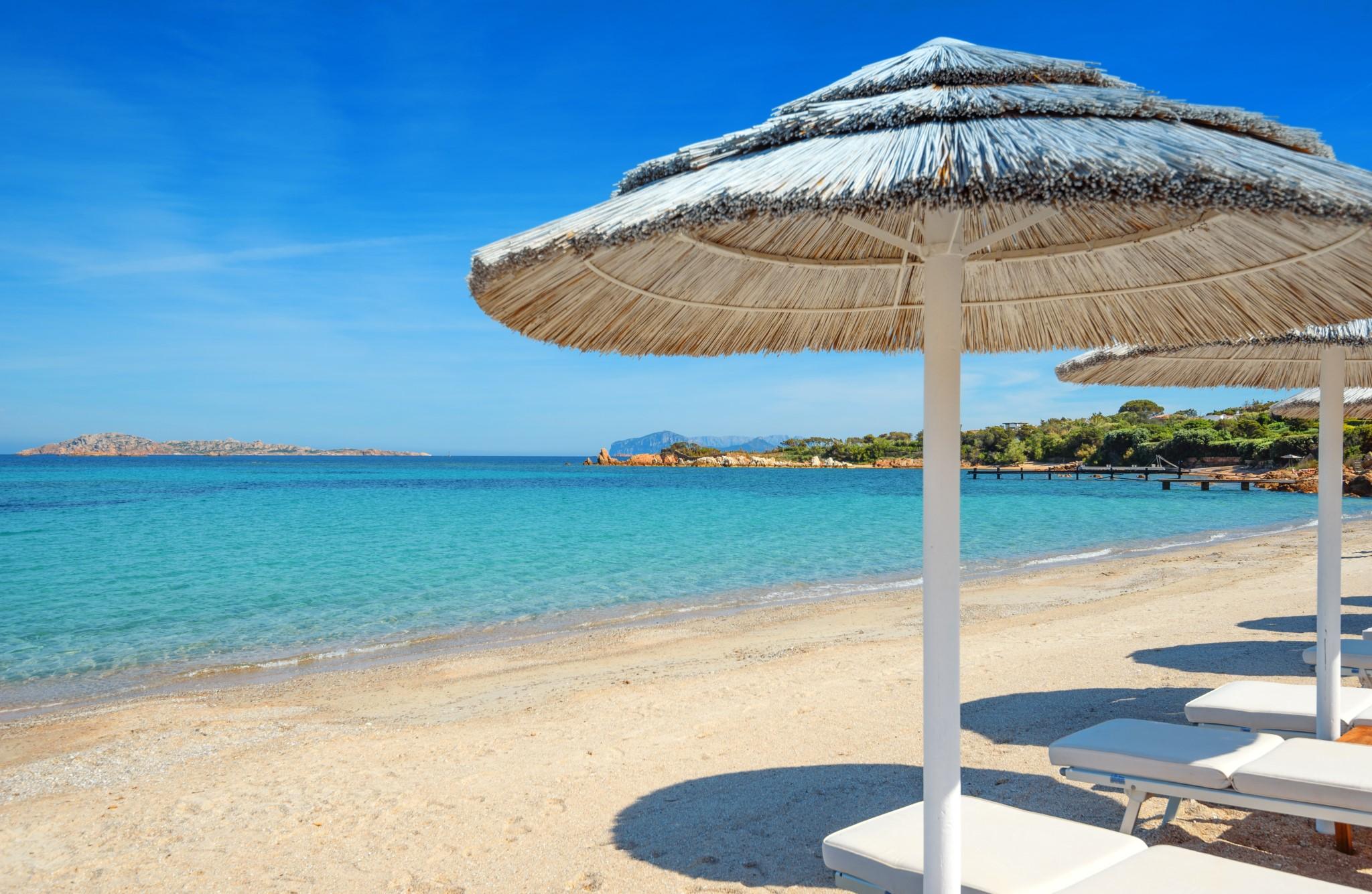 romazzino beach with white umbrellas,emerald coast of Sardinia,Italy