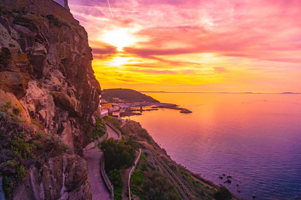 Beautiful alley of Castelsardo old town - Sardinia - italy. Colorful photo of gorgeous purple sunset in Sardinia island..