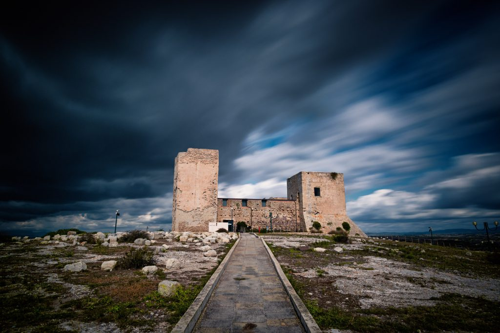 Castle of San Michele in Cagliari, Sardinia, in perspective with a stone road and a long exposure on a cloudy day.