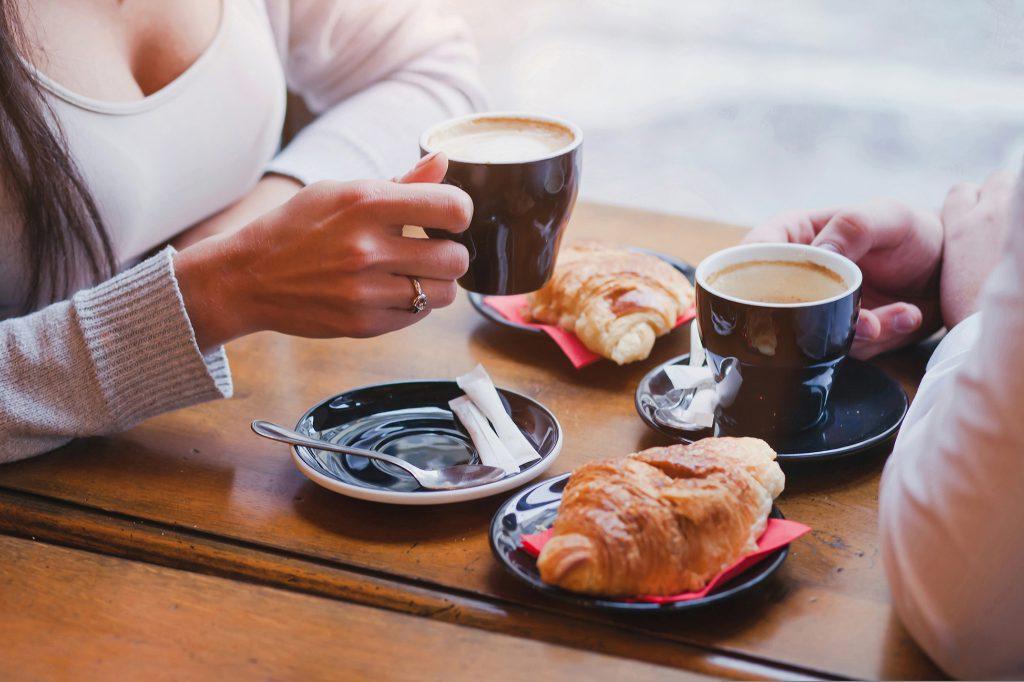 kawy i rogaliki w kawiarni, ręce pary zbliżenie