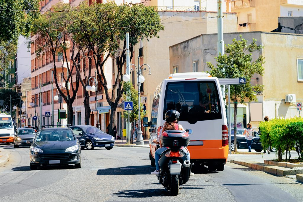 Street view on Road with cars, scooter and shuttle bus in Cagliari in Sardinia Island in Italy. Urban district