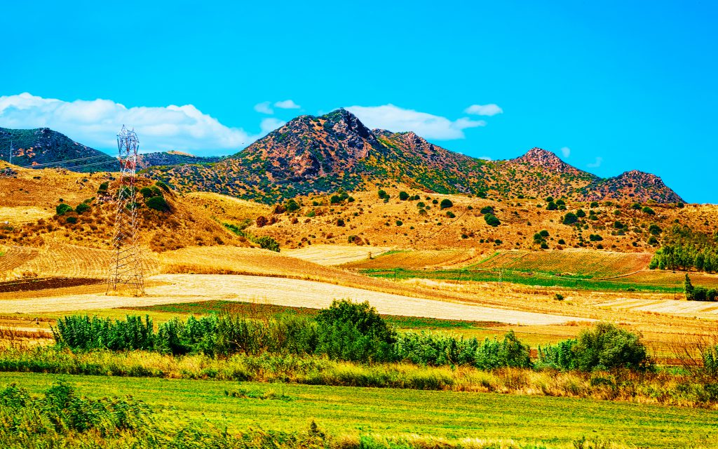 Agricultural fields in Nuoro at Mount Ortobene. Panorama and landscape in Sardinia island of Italy. Scenery of Sardegna in summer. Cagliari province. Mixed media.
