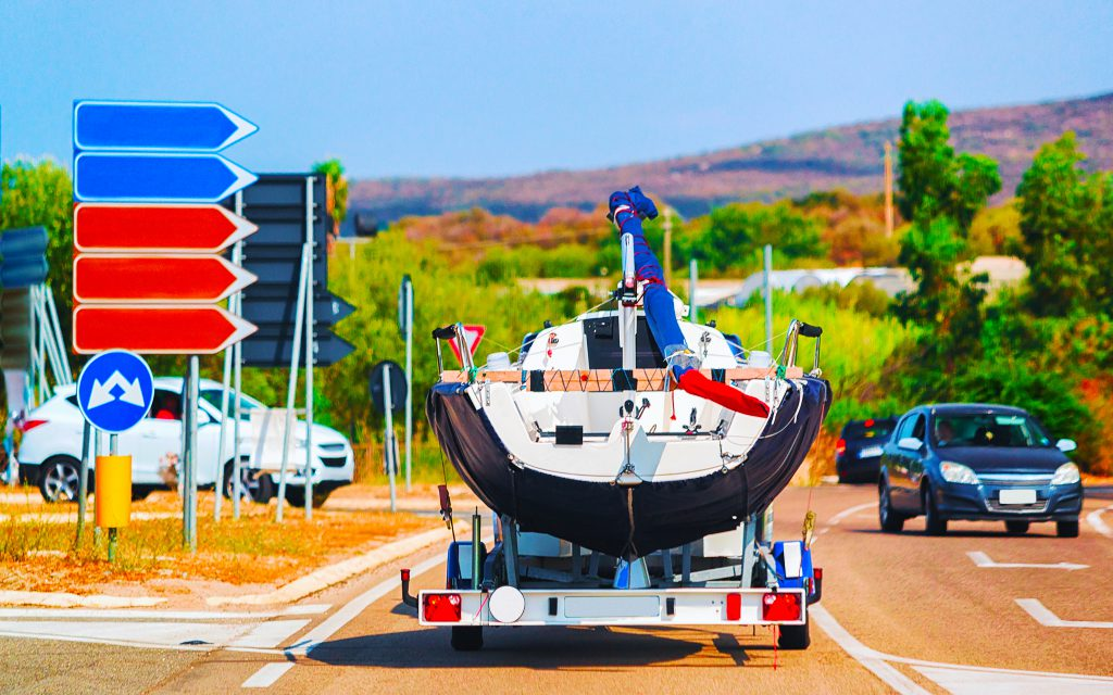 Car with a motor boat on the trailer on the road of Olbia, Costa Smeralda, Sardinia, Italy