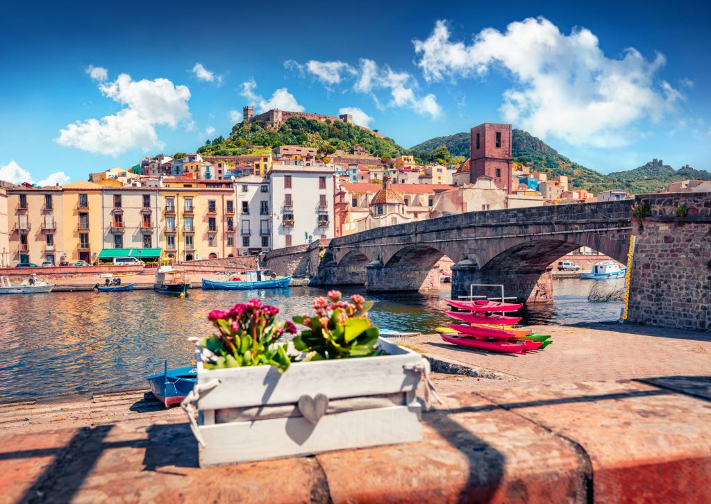 Colorful summer cityscape of Bosa town with Ponte Vecchio bridge across the Temo river. Stunning morning view of Sardinia island, Italy, Europe. Traveling concept background.