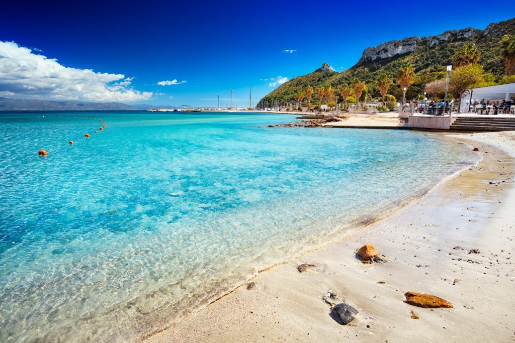 "Poetto's Beach with ""Sella Del Diavolo"" promontory on background in Cagliari, Sardinia in a clear sunny day"