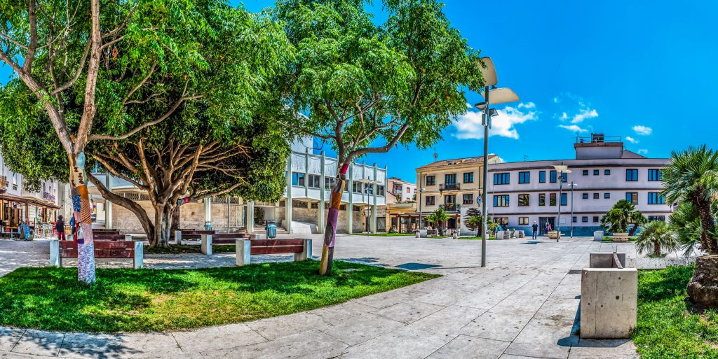 Porto Torres, Sardinia / Italy - May 30 2018: Square Umberto the first (Piazza Umberto I) in the city of Porto Torres, Sardinia, in a sunny day of spring