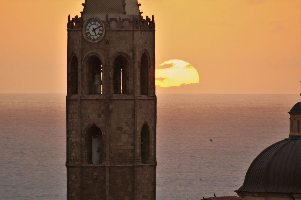 Sunset; close up of the Alghero Cathedral  bell tower (Santa Maria) and of the historic centre. Sardinia, Italy.